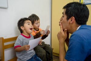 Comprehensive cleft care improves children's physical and psychological health dramatically. Speech therapist Renato Torres Calle (right) teaches two year olds Franco Alejandro Buendia Sanchez (left), and Jesus Alonso Trucios Pipa (centre), how to enunciate vowel sounds at a KusiROSTROS Community Rehabilitation Centre.